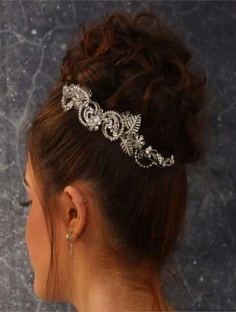 Rhinestone and pearl tiara shown here with a curly-bun hair-style.